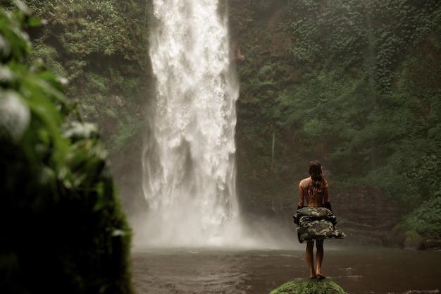Ragazza in posa sullo sfondo di una cascata