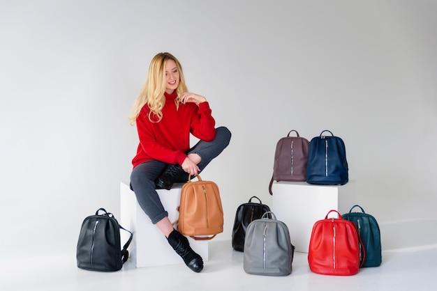 Ragazza in posa con un sacco di borse