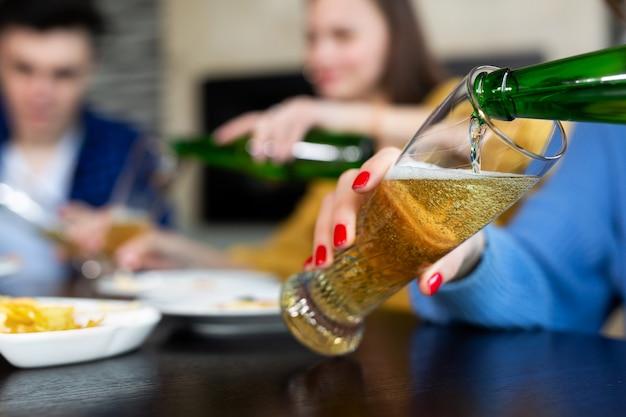 La ragazza versa la birra da una bottiglia in un bicchiere