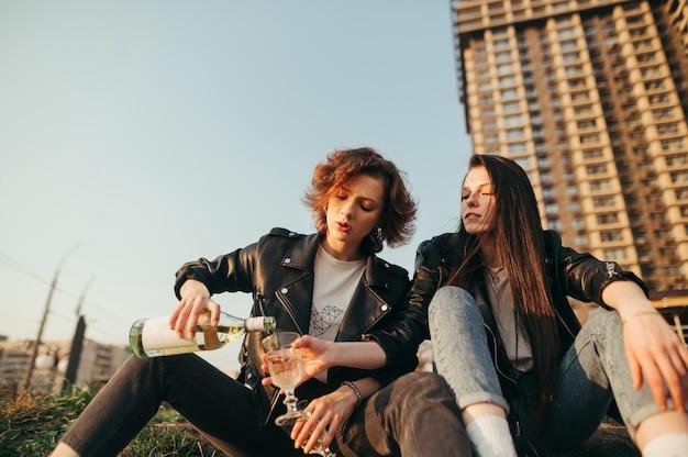 La ragazza versa il vino dalla bottiglia in vetro sulla strada sul paesaggio urbano