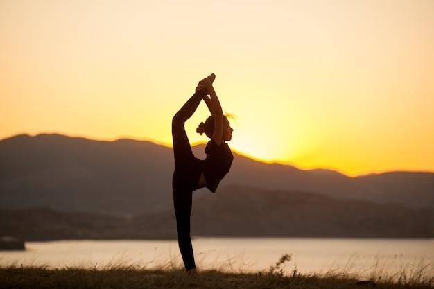 La ragazza pratica lo yoga in montagna sull'oceano.