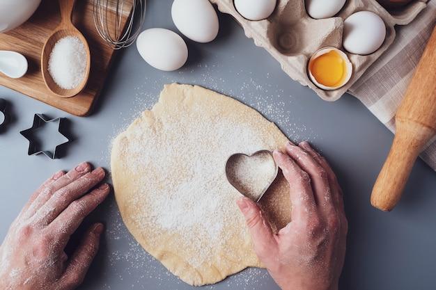 La ragazza prepara i biscotti a forma di cuore, composizione piatta su uno sfondo grigio. tagliabiscotti e pasta nelle mani delle donne. concetto di cibo per san valentino, festa del papà, festa della mamma.