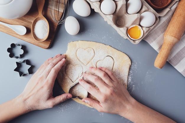 La ragazza prepara i biscotti a forma di cuore, composizione piatta laica su uno sfondo grigio.