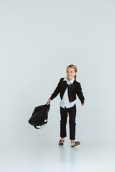 Ragazza che si prepara per la scuola dopo una lunga pausa estiva. di nuovo a scuola. piccola modella caucasica femminile in posa in uniforme scolastica con zaino su sfondo bianco. infanzia, istruzione, concetto di vacanze.