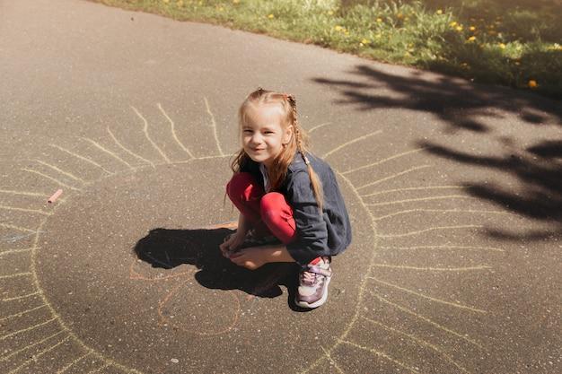 La ragazza in età prescolare disegna con il gesso sull'asfalto in estate nel parco