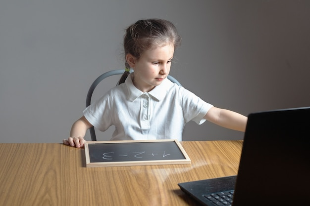 La bambina in età prescolare impara a casa a contare e scrivere numeri su una piccola lavagna.