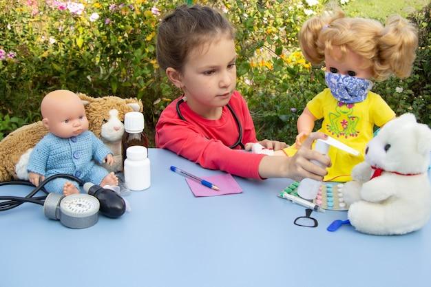 Una bambina in età prescolare spruzza con la medicina un orsacchiotto. un bambino gioca al dottore per strada.