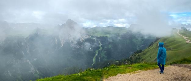 Una ragazza in un cappotto protettivo ammira il paesaggio di nuvole e montagne, dolomiti italiane