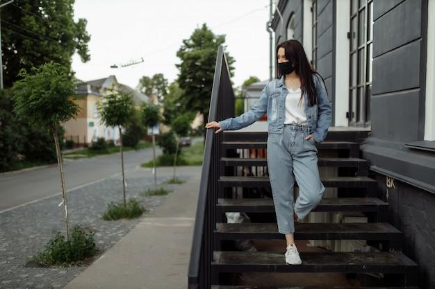 La ragazza in una maschera protettiva su un balcone guarda una città vuota.