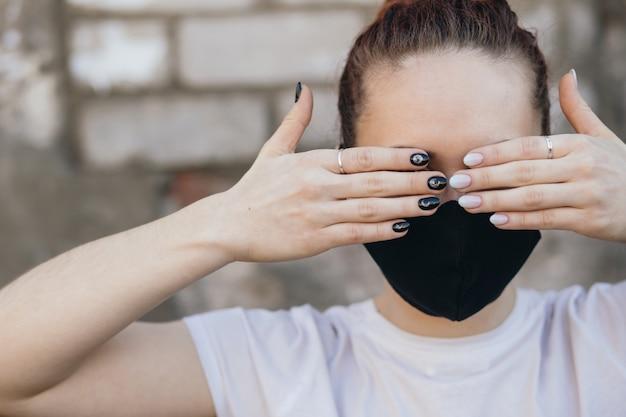 Una ragazza in una maschera protettiva si copre gli occhi con le mani