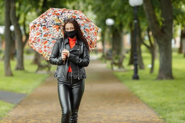 Ragazza con maschera protettiva cammina nel parco con un ombrello sotto la pioggia infezione da coronavirus covid