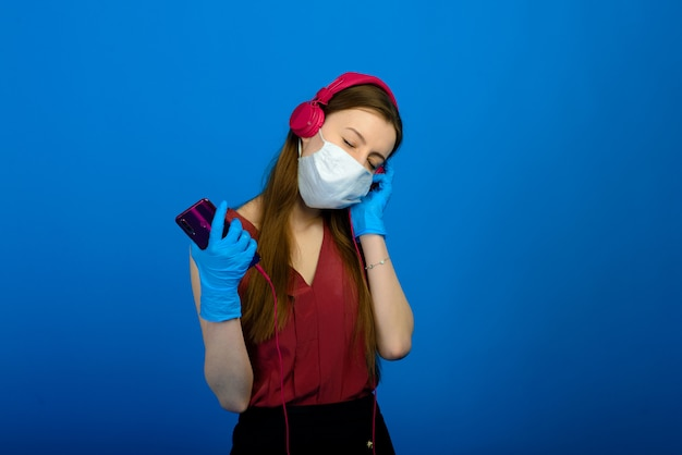Ragazza in maschera medica protettiva e guanti blu su sfondo blu. ritratto di close-up di una donna in una maschera trasparente.