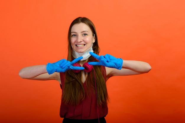 Ragazza in maschera medica protettiva e guanti blu sulla parete rossa. primo piano ritratto di una donna in una maschera trasparente. modo per proteggersi dal coronavirus. covid-2019, pandemia 2020