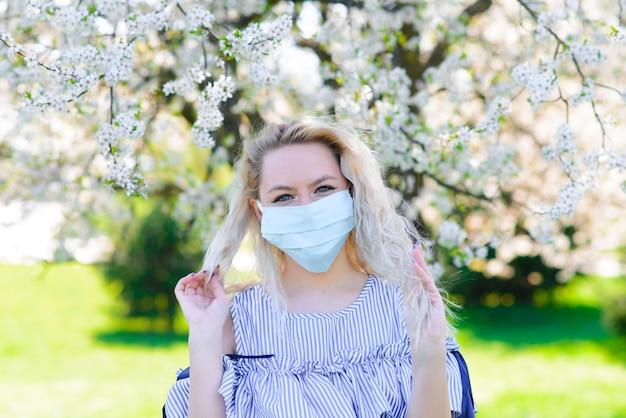 Una ragazza con una maschera medica protettiva in primavera tra il giardino fiorito. . concetto di covid primaverile.