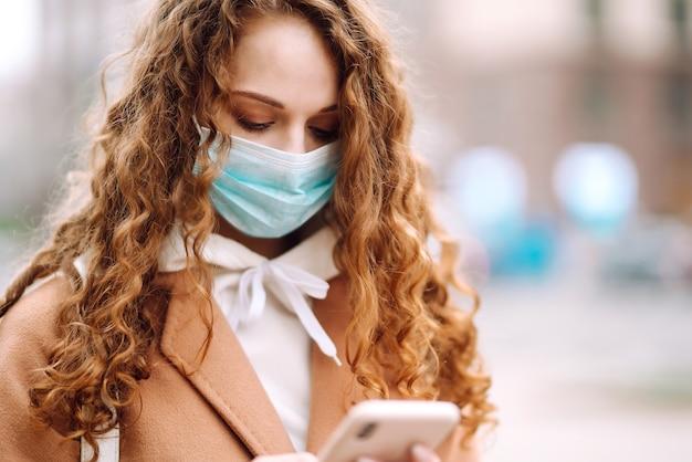 Ragazza in mascherina medica sterile protettiva sul viso con un telefono nella città di quarantena. donna che utilizza il telefono per cercare notizie.