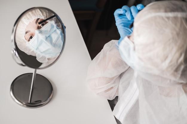 Ragazza in tuta protettiva, guanti di gomma blu, maschera medica e applica il trucco