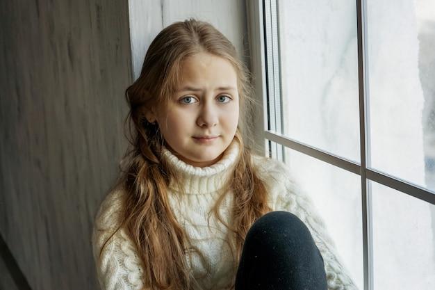 Ragazza in maglione seduta vicino alla finestra il bambino resta a casa durante le vacanze scolastiche
