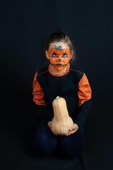 Una ragazza truccata da zucca per halloween è seduta sulle ginocchia e tiene una zucca tra le mani, isolata.