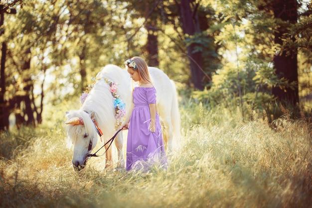 Ragazza in vestito viola che abbraccia unicorno bianco