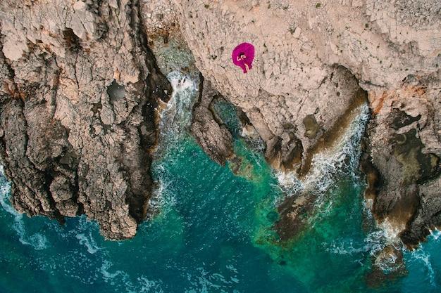 Una ragazza in un vestito viola riposa su una spiaggia rocciosa