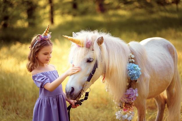Ragazza in abito viola con ghirlanda di un unicorno nei capelli che abbraccia e bacia unicorno bianco