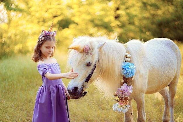 Ragazza in vestito viola con la corona di un unicorno in capelli che abbraccia un unicorno bianco