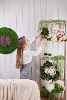 La ragazza mette i fiori sullo scaffale