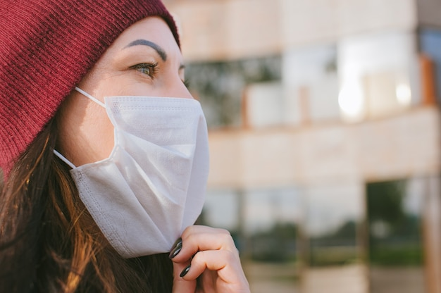 La ragazza indossa una maschera medica sul viso. sullo sfondo di un business center in vetro.