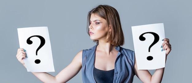 Domanda della ragazza. donna con espressione dubbiosa e punti interrogativi. donna pensante. ottenere risposte, pensare.