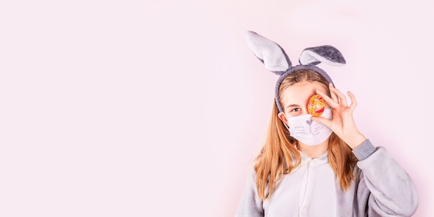 Ragazza in orecchie di coniglietto di coniglio sulla testa e maschera protettiva con uova colorate su sfondo rosa.