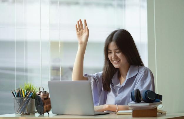 La ragazza alza la mano per rispondere alla domanda dell'insegnante a casa