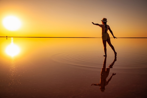 Una ragazza allunga le mani verso il sole al tramonto sulla superficie a specchio di un lago salato