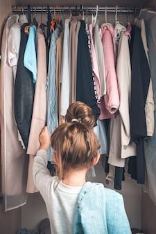 La ragazza cerca le cose nell'armadio.