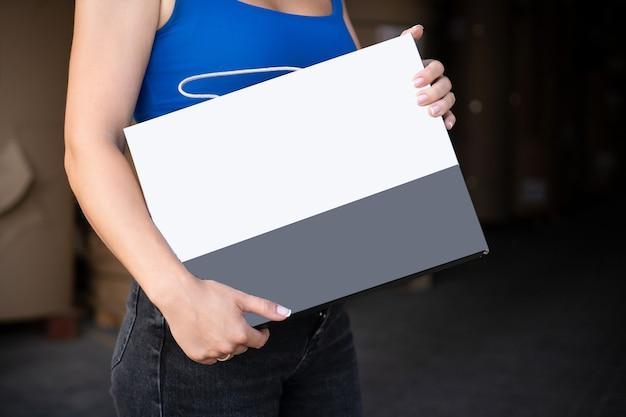 Ragazza che legge il libretto dell'opuscolo dell'aletta di filatoio nero in bianco. presentazione del volantino. opuscolo tenersi per mano. la donna mostra carta offset trasparente.