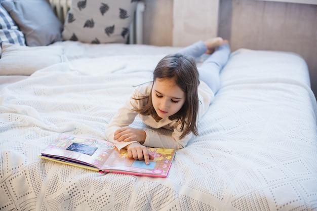 Ragazza che legge un libro sul letto a natale