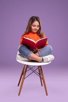 Libro di lettura della ragazza sulla sedia
