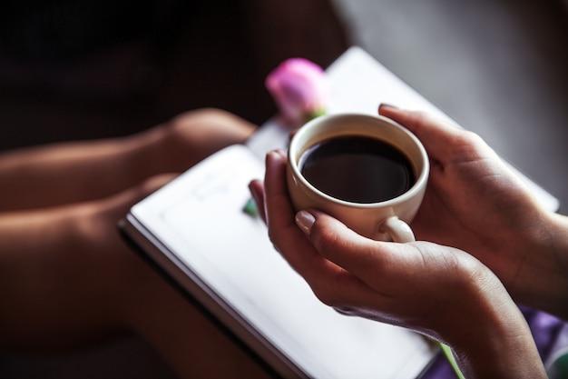 Libro di lettura della ragazza e bere caffè, bella rosa. mattina, hobby, fiori, studio