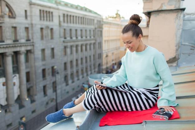 Ragazza che legge un libro sul tetto dell'edificio.