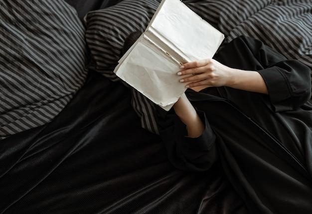 Ragazza che legge un libro mentre giaceva a letto in una vista dall'alto di una vestaglia.