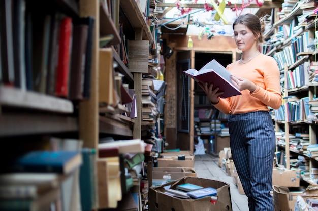 La ragazza legge il libro in biblioteca