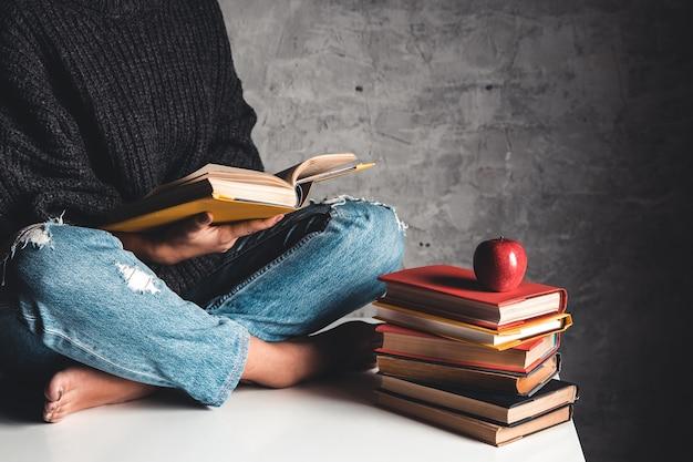 La ragazza legge libri, studia, sviluppa su un tavolo bianco e uno sfondo grigio.