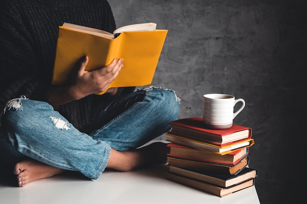 La ragazza legge libri, studia, sviluppa con una tazza di caffè su un tavolo bianco e uno sfondo grigio.