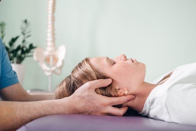Una ragazza che riceve un trattamento cst. manipolazione osteopatica e terapia cranio-sacrale per bambini e adulti