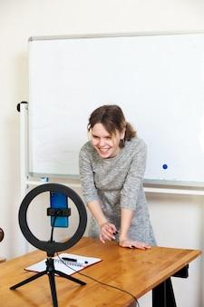 Ragazza che registra video su smartphone e si illumina con la lampada ad anello