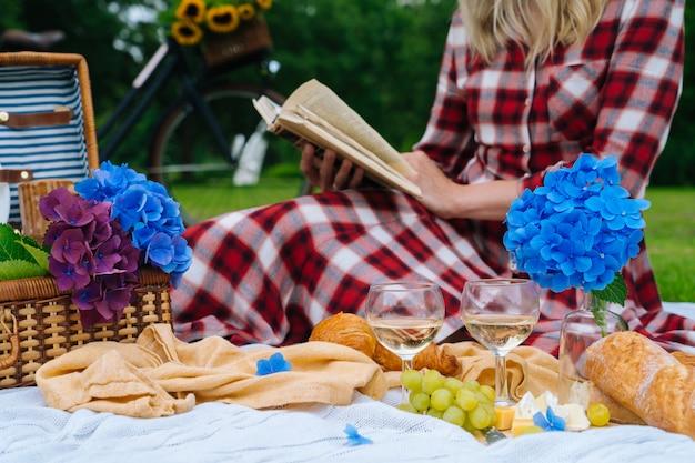 Ragazza in vestito a scacchi rosso e cappello che si siede sulla coperta da picnic in maglia bianca leggendo il libro e bere vino. picnic estivo in una giornata di sole con pane, frutta, bouquet di fiori di ortensie. messa a fuoco selettiva.