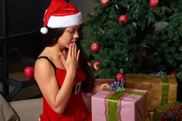 Una ragazza in un costume di natale rosso con regali nelle sue mani.