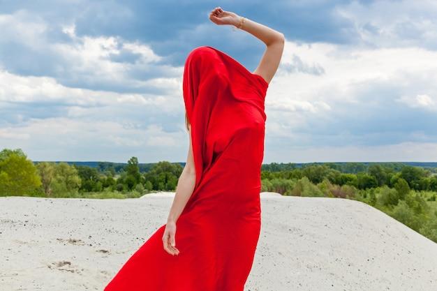 Una ragazza in un panno rosso sulla sabbia posa per un fotografo sullo sfondo di un cielo nuvoloso. il tessuto rosso al vento abbraccia la figura della ragazza.