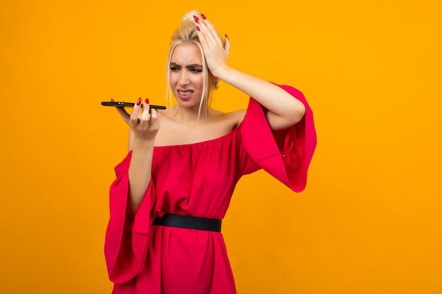 Ragazza in un vestito rosso che tiene la sua testa pensando di parlare al telefono su uno sfondo giallo