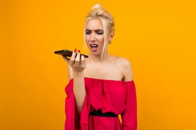 La ragazza in un vestito rosso parla indignato al telefono su uno spazio di studio giallo
