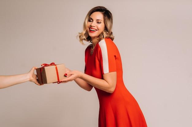 Una ragazza con un vestito rosso riceve un regalo tra le mani su un muro grigio.